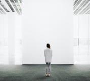 Ung kvinna som går till och med ett galleri och se royaltyfria bilder