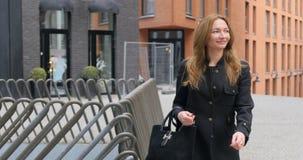 Ung kvinna som går vid väggen för röd tegelsten stock video