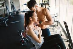 Ung kvinna som gör övningar för abs med den personliga instruktören Arkivfoton