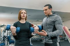 Ung kvinna som gör övningar med den personliga instruktören i idrottshall Sport, idrottsman nen, utbildning, sund livsstil och fo royaltyfri fotografi
