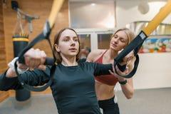 Ung kvinna som gör övningar med den personliga konditioninstruktören, övningar på konditionöglassystemet Sport idrottsman nen, ut royaltyfria bilder