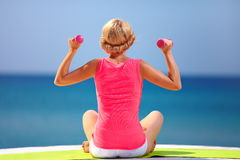 Ung kvinna som gör övningar med handvikter på stranden Royaltyfri Fotografi
