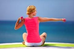 Ung kvinna som gör övningar med handvikter på stranden Arkivbilder