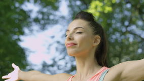 Ung kvinna som gör övningar, sträckning och yoga i en parkera under sommarmorgon stock video