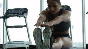 Ung kvinna som gör övningarna i idrottshallen stock video