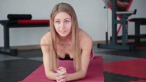 Ung kvinna som gör övningsplankan i idrottshall Flickan anstränger muskler av buk- press stock video