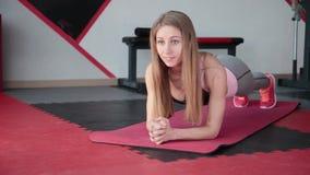 Ung kvinna som gör övningsplankan i idrottshall Flickan anstränger muskler av buk- press arkivfilmer