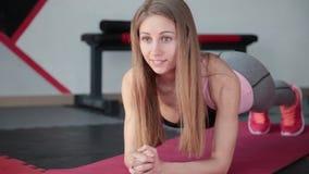 Ung kvinna som gör övningsplankan i idrottshall Flickan anstränger muskler av buk- press lager videofilmer