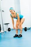 Ung kvinna som gör bodybuilding i idrottshallen Royaltyfria Bilder