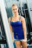 Ung kvinna som gör bodybuilding i idrottshallen Arkivfoton