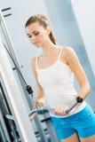 Ung kvinna som gör bodybuilding i idrottshallen Arkivfoto