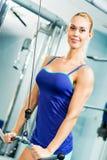 Ung kvinna som gör bodybuilding i idrottshallen Royaltyfri Foto