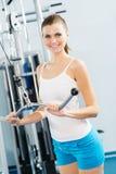 Ung kvinna som gör bodybuilding i idrottshallen Royaltyfria Foton