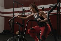Ung kvinna som gör cardio genomkörare genom att använda motionscykelen på crossfitidrottshallen royaltyfri fotografi