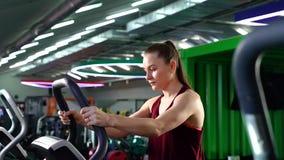 Ung kvinna som gör cardio genomkörare i idrottshall stock video