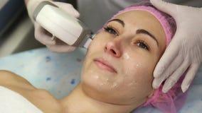 Ung kvinna som gör cosmetologylaser-terapi lager videofilmer