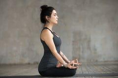 Ung kvinna som gör den Sukhasana övningen, sidosikt royaltyfri foto