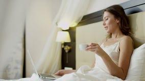 Ung kvinna som gör den videopd översättningen på hennes bärbar dator, medan dricka kaffe i säng stock video