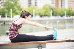Ung kvinna som gör elasticiteter på trä, bänk. Arkivfoto
