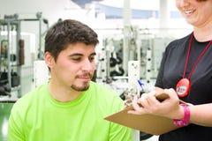 Ung kvinna som gör ett utbildningsplan till en man på idrottshallen Royaltyfria Bilder