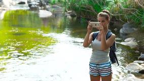 Ung kvinna som gör fotonaturlandskap på mobiltelefonen, medan resa i turist- skytte för tropisk skogkvinna lager videofilmer