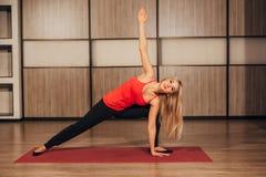 Ung kvinna som gör hemmastadd idrottshall för yoga arkivfoto