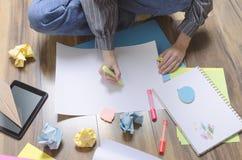 Ung kvinna som gör hennes eget starupplan och ner skriver huvudsakliga första steg Begreppet av startar upp royaltyfri bild