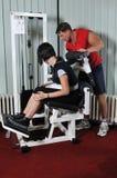 Ung kvinna som gör kondition i idrottshall Arkivfoto