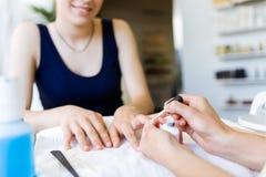 Ung kvinna som gör manikyr i salong pärlor för blå för begrepp för bakgrundsskönhet blir grund naturliga over för behållare kosme Royaltyfri Bild