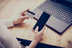 Ung kvinna som gör online-shopping vid bärbara datorn och smartphonen Flicka som hem trycker på knappen på mobiltelefonen som skr Royaltyfri Foto