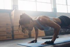 Ung kvinna som gör push-UPS på idrottshallen Arkivfoto