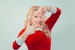 Ung kvinna som gör ramen med händer som ser kameran arkivfoto