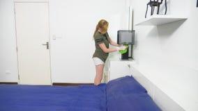 Ung kvinna som gör ren sovrummet med lokalvårdprodukter och utrustning, hushållsarbetebegrepp lager videofilmer
