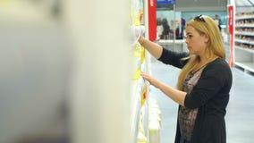 Ung kvinna som gör shopping i supermarket lager videofilmer