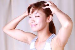 Ung kvinna som gör självhuvudmassage royaltyfri fotografi