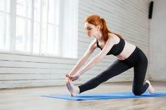Ung kvinna som gör sträcka övning i idrottshallen fotografering för bildbyråer