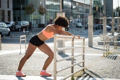 Ung kvinna som gör sträcka övning utomhus Royaltyfri Bild