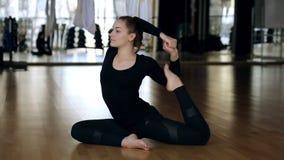 Ung kvinna som gör uppvärmningssammanträde på golv i modern sportklubba arkivfilmer