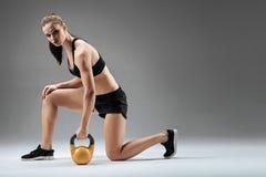 Ung kvinna som gör utfall med vikt Arkivfoto