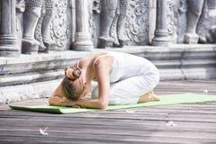 Ung kvinna som gör yoga i övergiven tempel på träplattformen övning royaltyfri foto