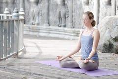 Ung kvinna som gör yoga i övergiven tempel på träplattformen övning royaltyfria foton