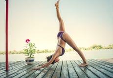 Ung kvinna som gör yoga i bikini på träflodflotten Royaltyfri Foto