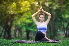 Ung kvinna som gör yoga i parkera Royaltyfri Fotografi