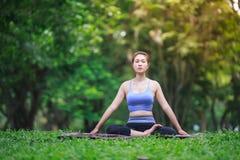 Ung kvinna som gör yoga i parkera Royaltyfria Foton