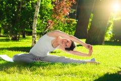 Ung kvinna som gör yoga i parkera i morgonen Royaltyfri Bild