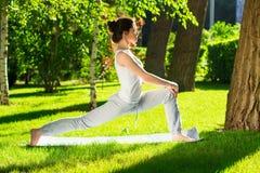 Ung kvinna som gör yoga i parkera i morgonen Fotografering för Bildbyråer