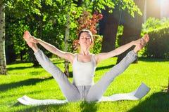 Ung kvinna som gör yoga i parkera i morgonen Arkivfoto