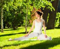 Ung kvinna som gör yoga i parkera i morgonen Royaltyfria Foton