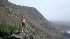 Ung kvinna som gör yoga på en stenig kust på solnedgången Begreppet av en sund livsstil harmoni mänsklig natur _ arkivfilmer