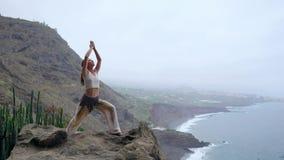 Ung kvinna som gör yoga på en stenig kust på solnedgången Begreppet av en sund livsstil harmoni mänsklig natur _ stock video